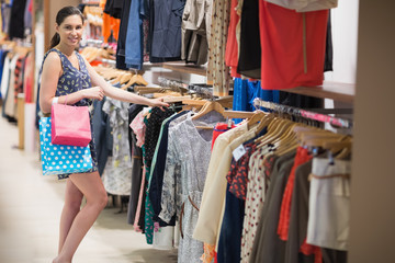 Woman searching through clothes rail while holding two bags