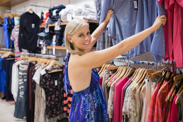 Woman looking through clothes and smiling
