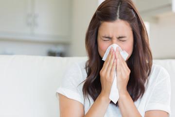 Fototapeta Brunette sneezing in a tissue obraz
