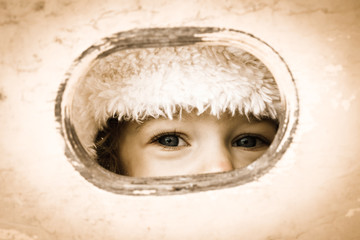Child looking through hole