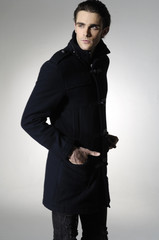 Fashion portrait of handsome young man model in black coat
