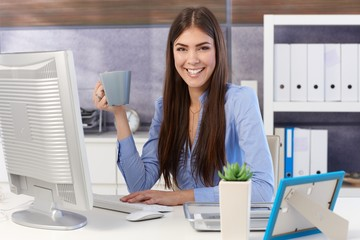 Happy businesswoman in office with coffee