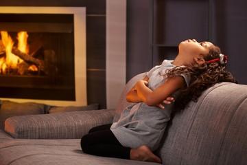 Little girl sulking on sofa