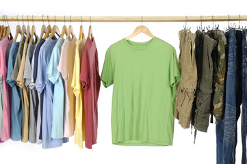 Choice of casual clothes on wooden hangers and trousers