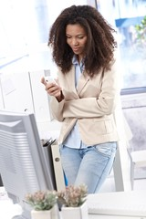Pretty office worker texting on mobile phone