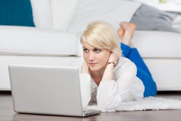 blonde frau liegt mit ihrem laptop auf dem fußboden
