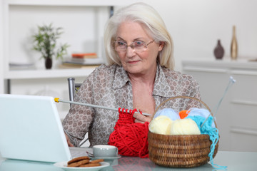 Older woman knitting at a laptop