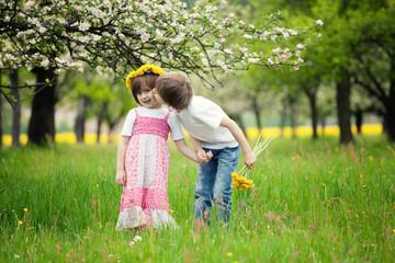 Children kissing in meadow