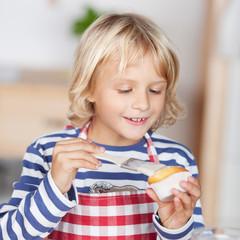 mädchen bestreicht muffin mit zuckerguss