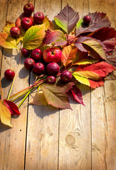 Autumn  apples and fallen leaves on old wooden table