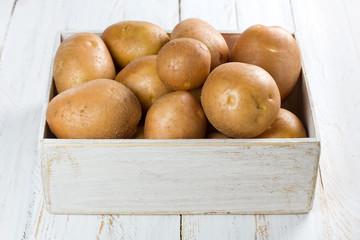 Potato in a shabby wooden box