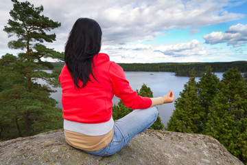 Young brunette at meditation in idyllic scenery of Sweden