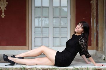 Ragazza con vestito nero davanti alla porta