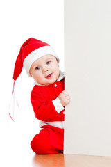 small Santa claus child looking from behind the placard