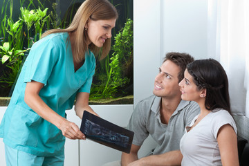 Dentist Showing Dental X-Ray To Couple