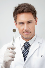 Young Male Dentist Holding Tools