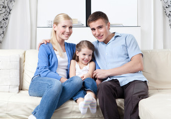 Family of three hug each other on the white leather sofa