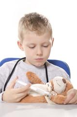 chłopiec z misiem udający lekarza