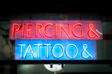 Neon signboard with Piercing & Tattoo at night.
