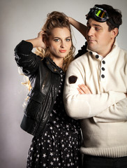 Young couple in retro style clothes over light background