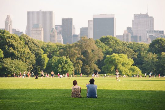 People enjoying relaxing outdoors in Central Park, NYC.
