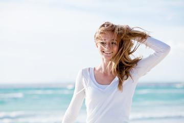 junge hübsche frau spaziert am strand im sand im freien im Somm