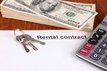 Rental contract with dollars on wooden background close-up