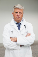 Serious doctor with folded arms