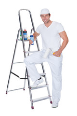 Painter Holding A Paint Roller And Paint Bottle