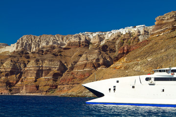 Boat at high volcanic cliff of Santorini island in Greece