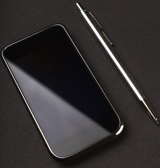 smartphone and pen on black background