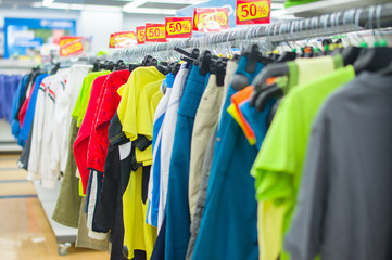 Color T-shirts and sport trousers on stands in supermarket