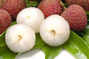 Lychee and peeled lychee on leaf