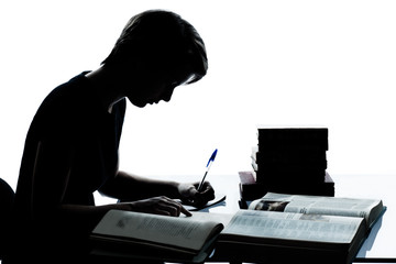 one young teenager boy or girl silhouette studying reading books