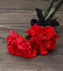 Foto op Textielframe Rood, zwart, wit carnations and black ribbon on grey wooden background