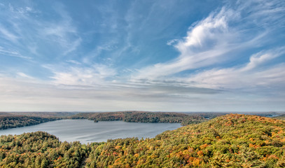 Fototapete - Lake Surrounded by Fall Trees and Whispy Clouds