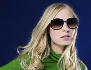 Fashion model in sunglasses. Posing in studio