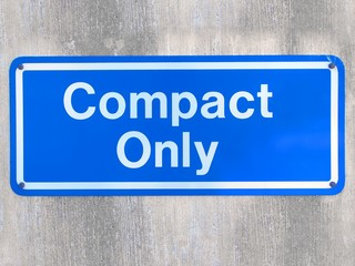 Compact car only / warning, blue metal sign against wall