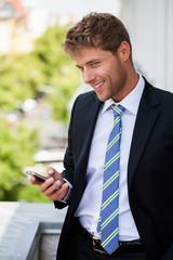 erfreuter Geschäftsmann mit Handy