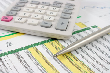 calculator and silver pen on financial data