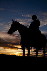 Fototapete - Cowboy sitting on horse in sunset