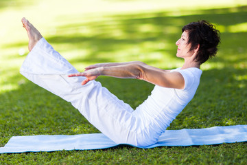middle aged woman doing yoga pose outdoors