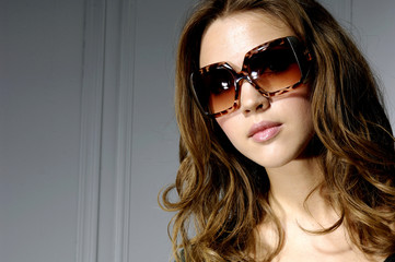 fashion shot of sexy girl with sunglasses on gray