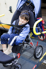 Disabled little boy on school bus wheelchair lift