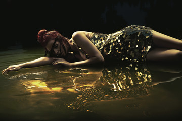 Attractive lady lying in liquid chocolate