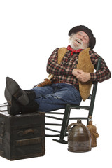 Happy old cowboy sits in rocking chair with feet up