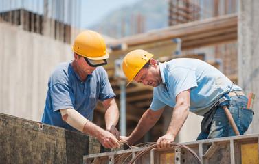 Fototapeta Construction workers working on cement formwork frames obraz
