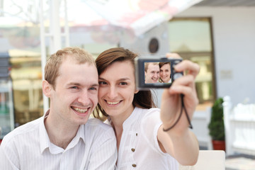 A young  couple  taking their photo on a digital camera