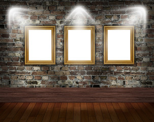 Three gold frames on brick wall in grunge room