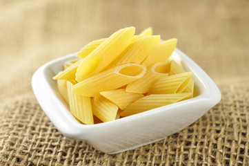 Several penne pasta in a small bowl